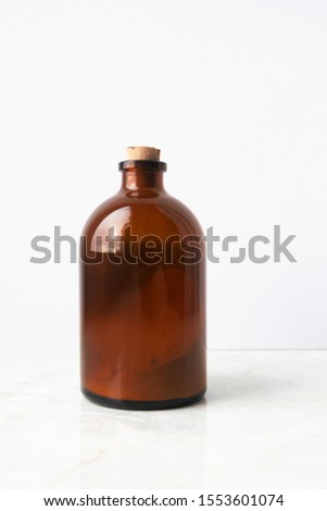 Glass brown bottle with organic ubtan powder on white background, vertical. Hand made organic skin care product, body cleanser and scrub
