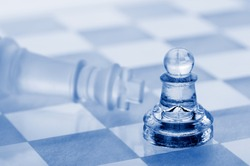 Glass chess. A victory of a pawn over a king. Blue toned.