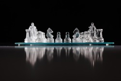 glass chess board with chess pieces on.