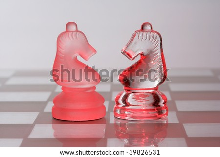Glass chess knights standing face to face in red light
