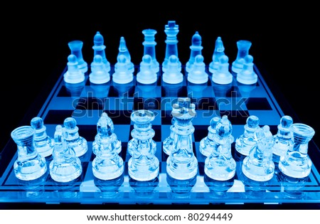 glass chess pieces before the game blue toned