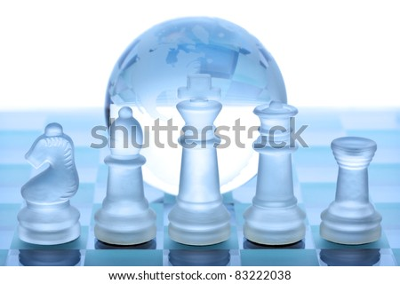 Glass chess pieces, board and globe concept for global business