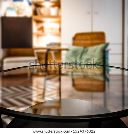 Glass coffee table of free space for your decoration. Blurred background of home interior and fall time. Warm mood photo style.  #1524376322
