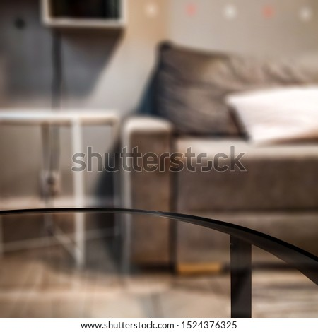 Glass coffee table of free space for your decoration. Blurred background of home interior and fall time. Warm mood photo style.  #1524376325