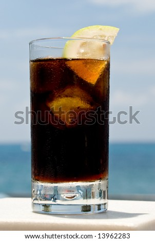 glass cola with ice - on the sea