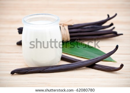 Glass container of yogurt with fresh vanilla beans on leaf and bamboo mat.