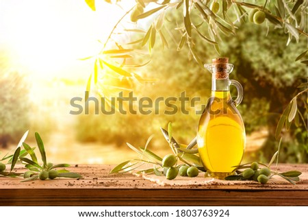 Glass container with olive oil on wooden table with branches and olives in crop field full of olive trees with sunshine