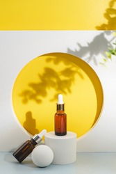 Glass cosmetic bottle with oil or serum for skin care on special podium on yellow background. Shadows Natural skin care concept. Harsh shadows