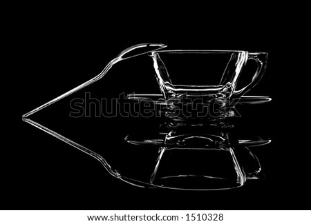 Glass cup and saucer with plastic spoon shot on black plastic and a black background.