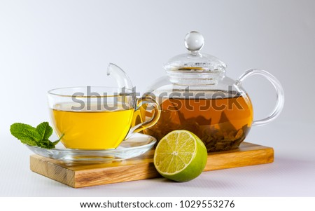 Glass cup and teapot of green tea, mint leaves and lime on a wooden board on a white background