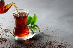 Glass cup of black tea pouring from teapot with fresh tea leaves, traditional turkish brewed hot drink