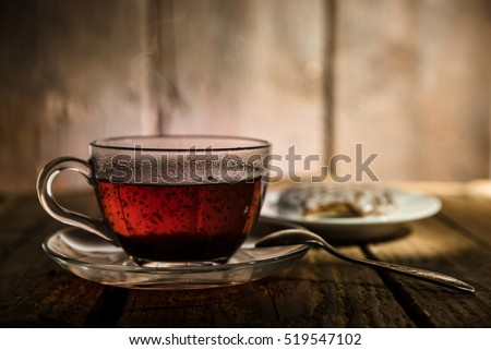 Glass cup of black tea, teaspoon and honey cake on wooden table