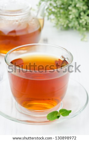 Glass cup of black tea with mint and teapot closeup