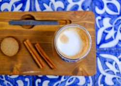 Glass cup of coffee cappuccino, cinnamon sticks and cookies on wooden tray and traditional white blue Portuguese tile table.