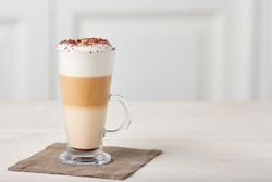 Glass cup of coffee latte on wooden table