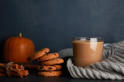 Glass cup of coffee with milk, grey knitted scarf, cookies, spices, orange pumpkin on black table against dark blue wall background. Autumn drink concept. Fall, spicy latte, thanksgiving, coffee shop