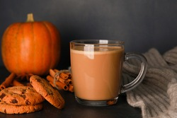 Glass cup of coffee with milk, grey woolen scarf, cookies, spices, pumpkin on black table against dark blue wall. Autumn drink concept. Fall, spicy latte, thanksgiving, coffee shop menu, closeup