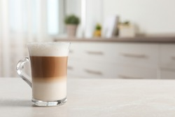 Glass cup of delicious layered coffee on light marble table indoors, space for text