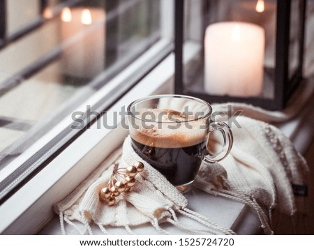 Glass cup of fresh strong americano coffee on marble windowsill in  winter morning with cinnamon stick, Christmas cozy garland bokeh twinkling lights, lantern and white cable knit scarf, copy space