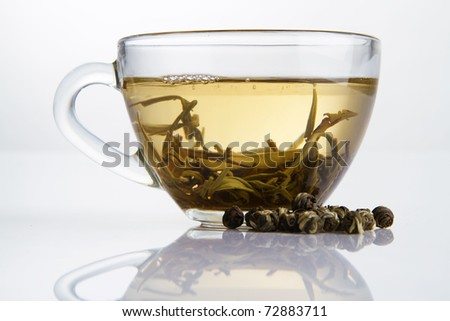 Glass cup of fresh white tea with dry tea granules