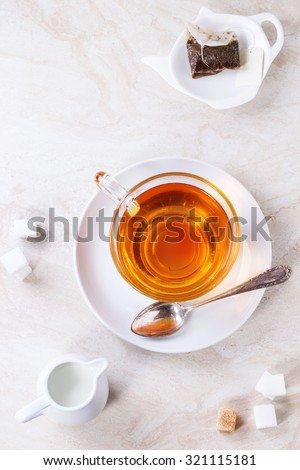 Glass cup of hot tea on saucer with sugar cubes, jug of milk and tea bag over white marble backgtound. Top view #321115181