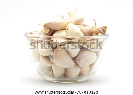 Glass cup of rood garlic, on white background