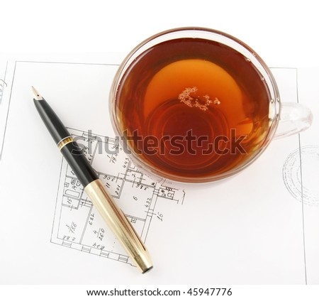 Glass cup of tea and pen on house plan