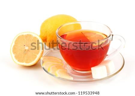 Glass cup of tea near two yellow lemons.