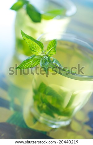 Glass cup of tea with a fresh mint on exotic background