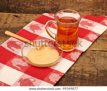 glass cup of tea with honey on colorful napkin