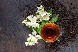 Glass cup of tea with jasmine flowers on dark background. Top view.