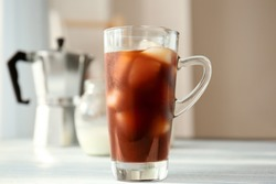 Glass cup with cold brew coffee on light background