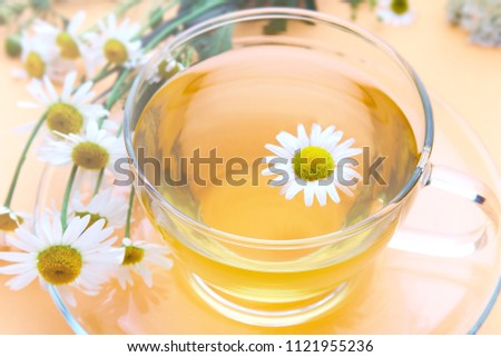 glass cup with decoction of chamomile on a yellow background