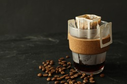 Glass cup with drip coffee bag and beans on black table, closeup
