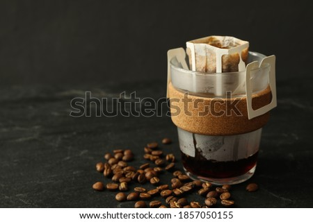 Photo of  Glass cup with drip coffee bag and beans on black table, closeup