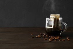 Glass cup with drip coffee bag and beans on black wooden table. Space for text