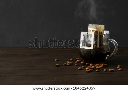 Photo of  Glass cup with drip coffee bag and beans on black wooden table. Space for text