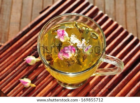 Glass cup with fresh green tea and dry roses