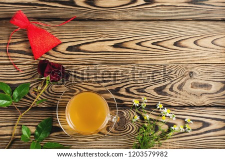 Glass cup with green tea near red rose and gift and bunch of chamomile on old wooden table. Top view. Saint Valentine's Day concept #1203579982