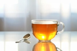 Glass Cup with tea on a glass table