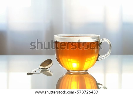 Glass Cup with tea on a glass table #573726439