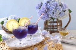Glass cups of Butterfly pea iced tea with lemon. Summer refreshing drink.
