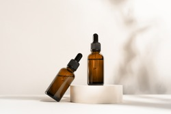 Glass dropper bottles with a pippette with black rubber tip on the beautiful shadow background. Nature Skin concept. Organic Spa Cosmetics. Trendy concept.