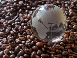 Glass earth globe Africa and Asia in centre closeup among coffee beans background. African countries exporters of cofe beans