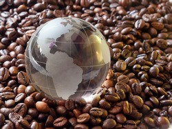 Glass earth globe South America in centеr closeup among coffee beans background. South american countries exporters of cofe beans