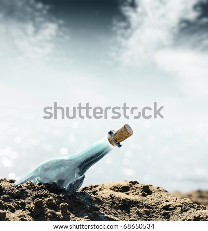 Glass empty bottle in coast sand and sky with clouds