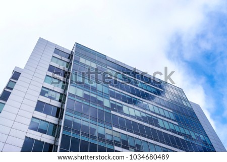 Glass facade of the building with a blue sky and white clouds