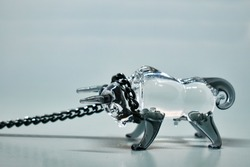 Glass figurine of a bull with a black metal chain around the neck. Gray background. Bull on a chain. Selective focus. Symbol of 2021. The concept of resistance, stubbornness, overcoming difficulties