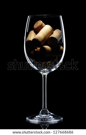 glass filled with corks on a black background