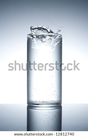 Glass filled with water with splash on a reflecting surface